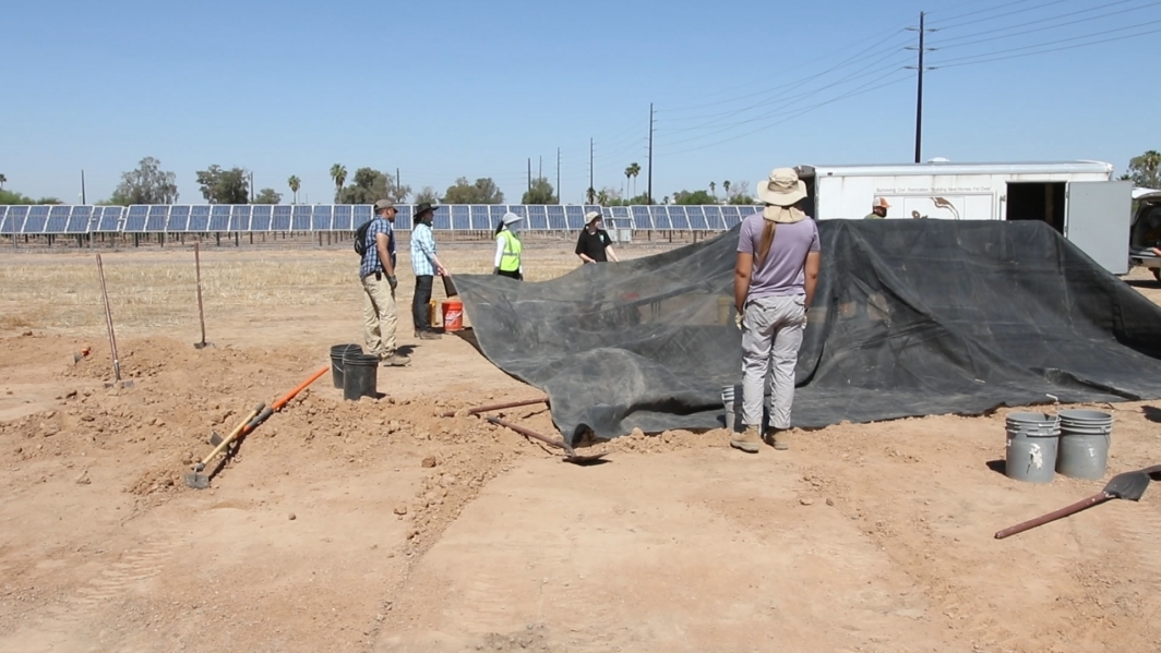 Volunteers stretch sturdy shade cloth over tent poles