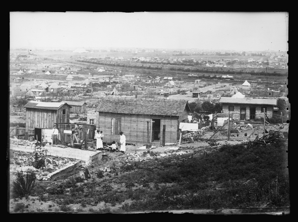 historical photo of small wood building being built on hill