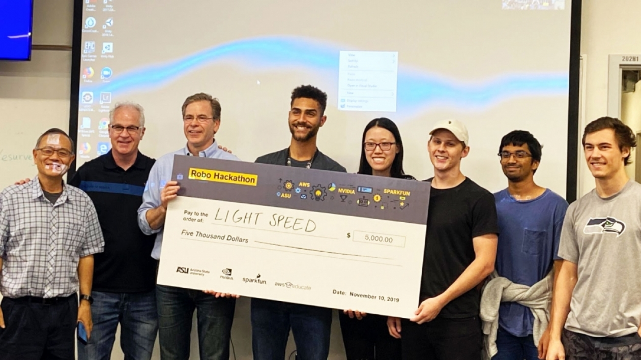 Team Light Speed holds their oversized check