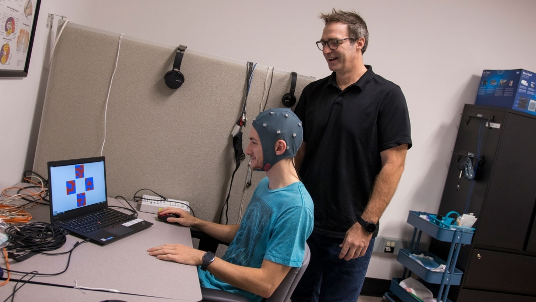 """Associate Professor William """"Jamie"""" Tyler (standing) works with a student in the Tyler Neurotechnology Lab."""