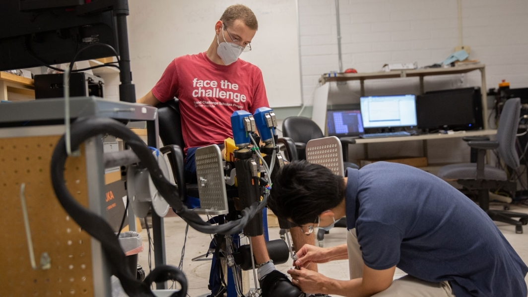 Connor Phillips tests a robotic device with Hyunglae Lee.
