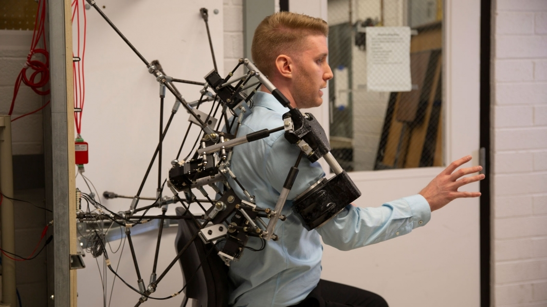 A student demonstrates a wearable robotic-aided rehabilitation framework on his shoulder for exercise therapy.
