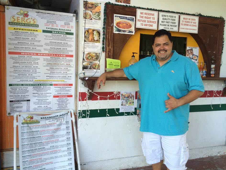 man standing at counter of taco shop