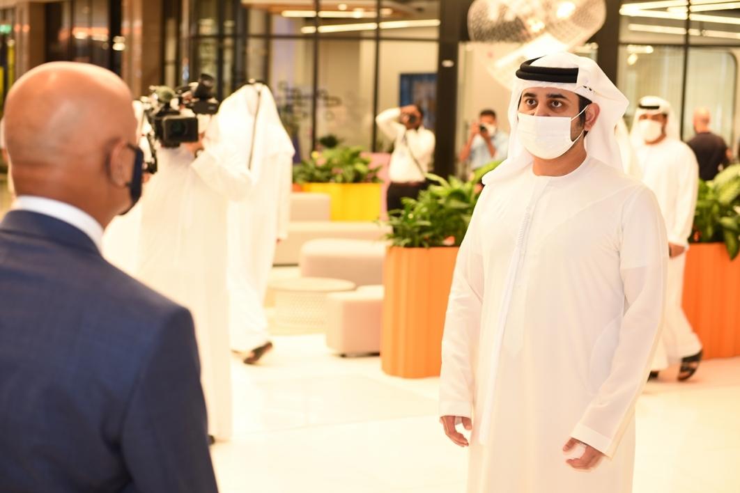 Sheikh Maktoum bin Mohammed wearing a face covering while speaking with Thunderbird Dean Sanjeev Khagram