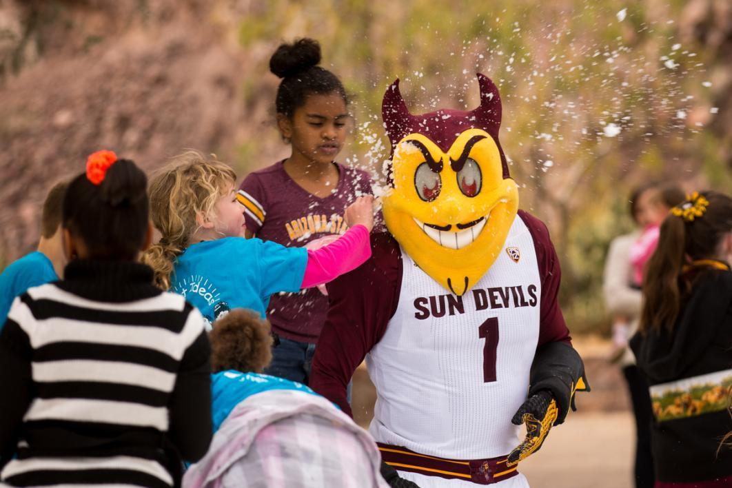 Kids attack a mascot with snow.