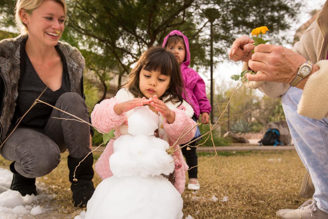 Child builds a snowman.