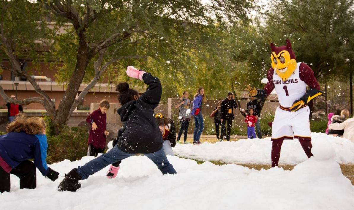 Children pelt a mascot with snowballs.