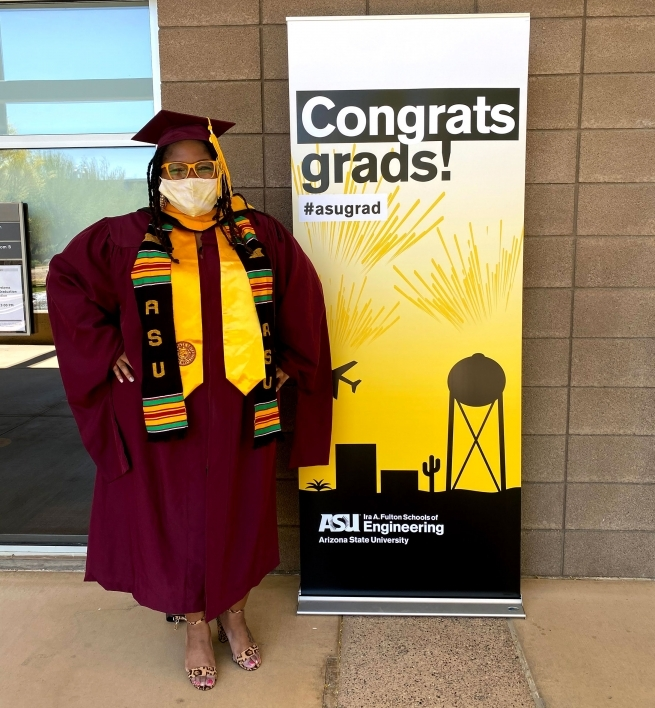 A woman in graduation robes poses in front of a sign that says Congrats, grads!