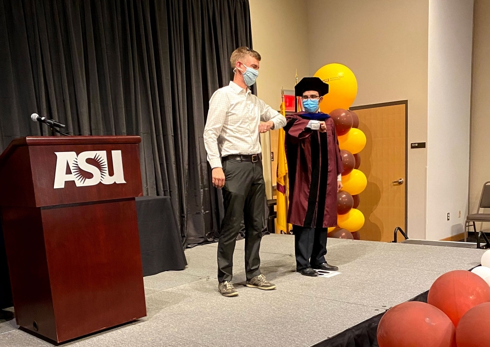 A student in PhD commencement robes bumps elbows with his adviser on stage