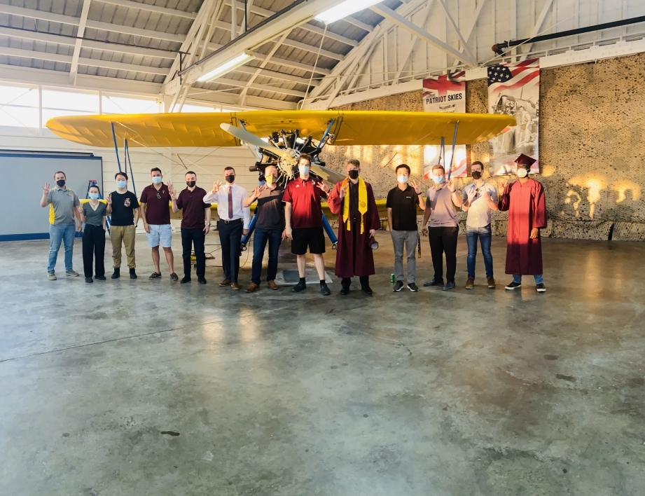 Students line up in front of an old prop plane inside a hangar