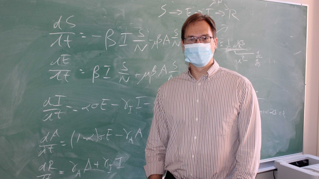 Steffen Eikenberry stands in front of a chalkboard with equations written on it