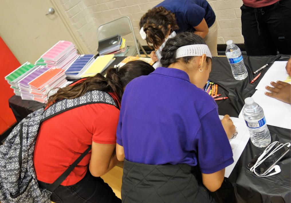 Health fair participants draw and journal as part of the stress management lesson
