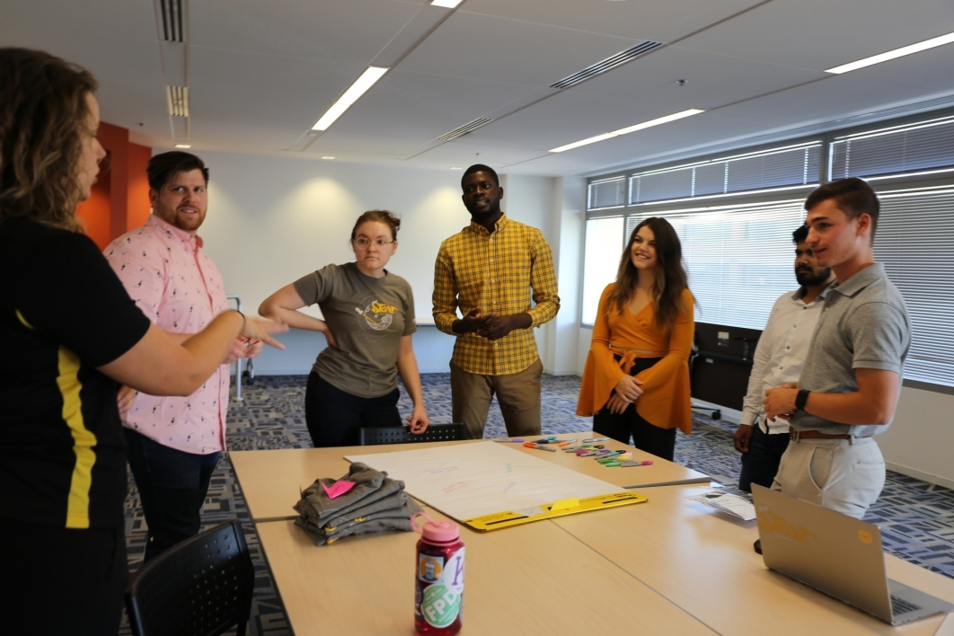 A group of students discuss ideas around a table