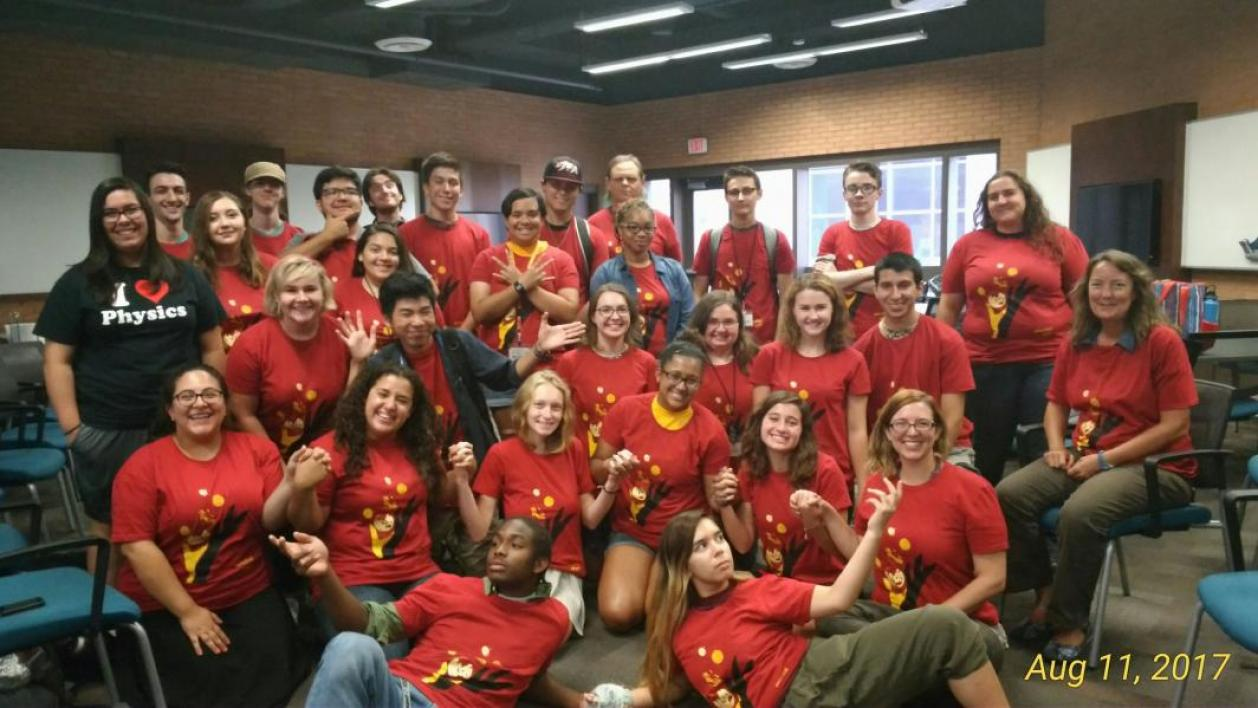 group of people wearing red shirts posing for photo