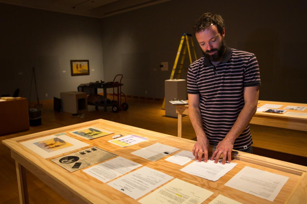 Man looking at documents in a gallery.
