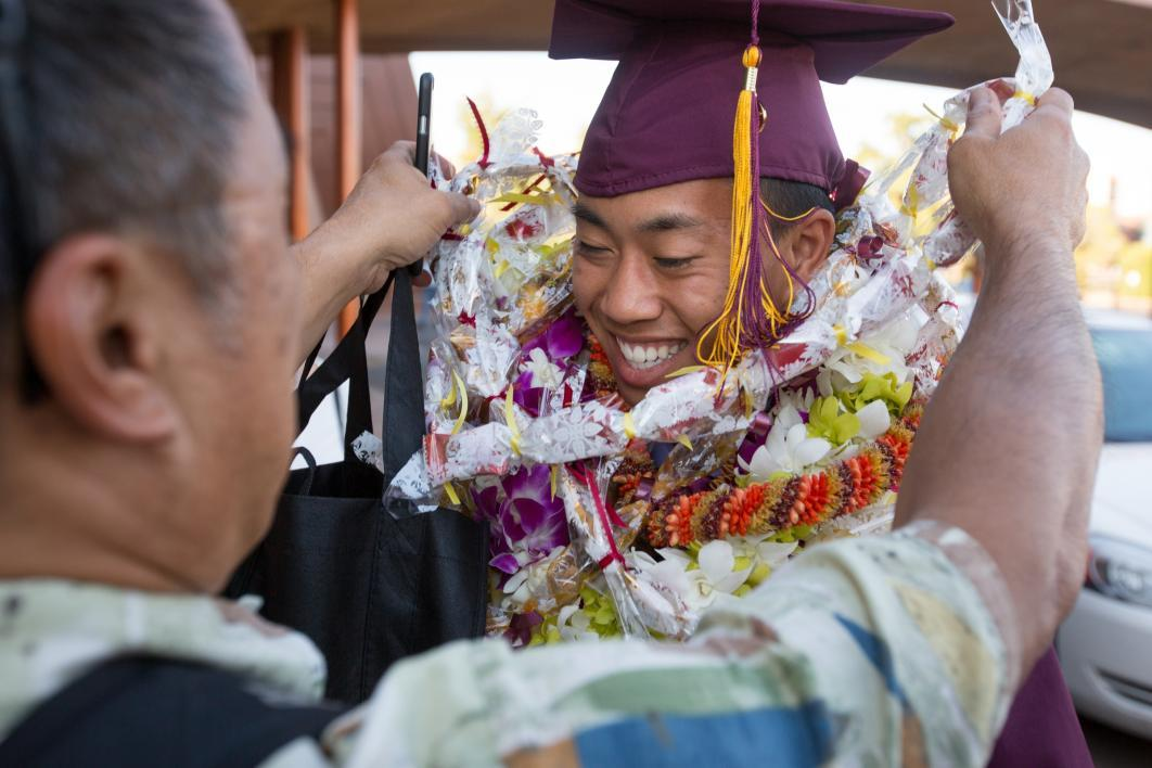 father giving graduate lei