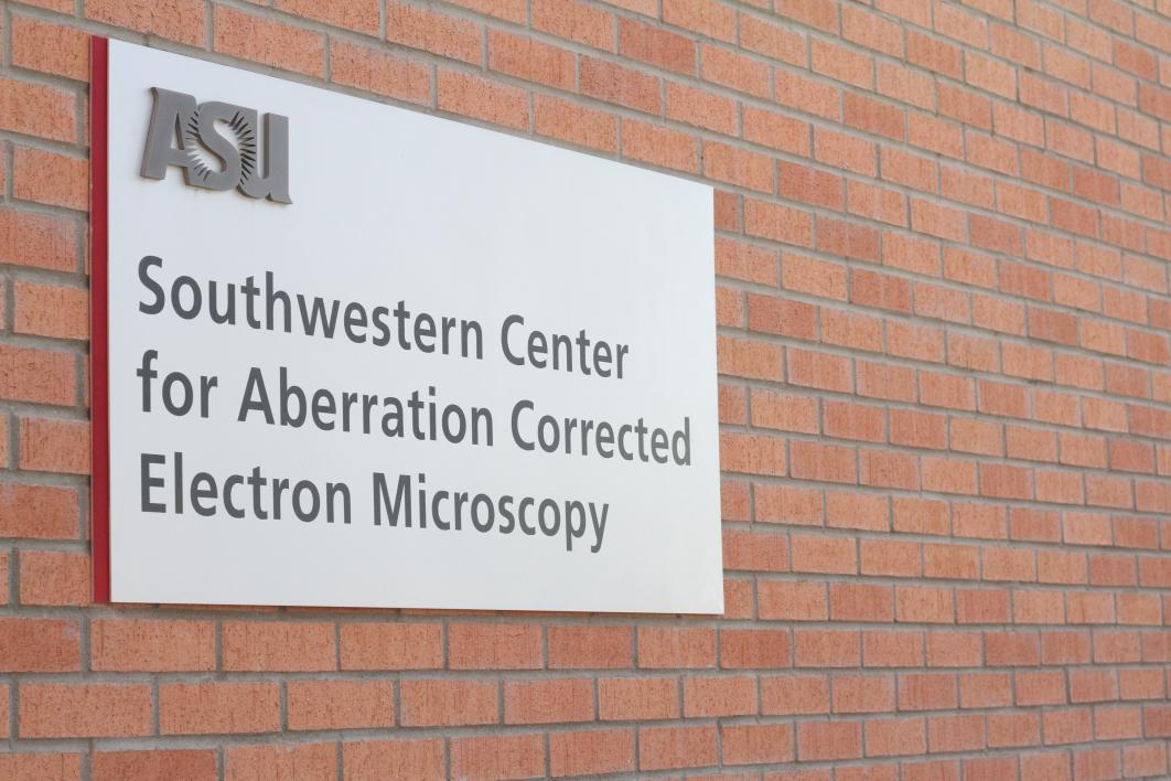 A sign on a brick wall for an electron microscopy center