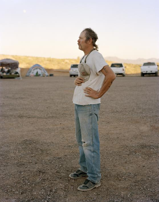 Photo by Pam Golden shows a white man with a ponytail, wearing faded jeans and a t-shirt, standing in profile with his hands on his hips.