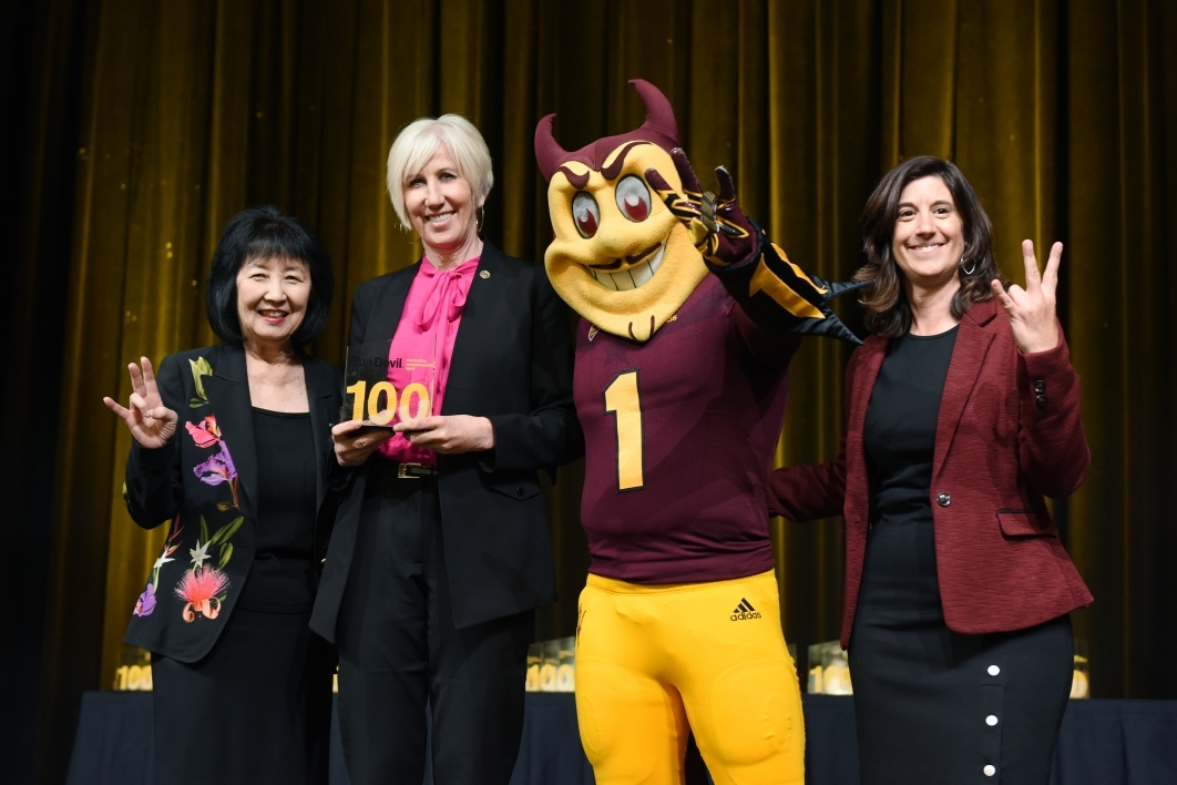three women pose on stage with ASU mascot Sparky the Sun Devil