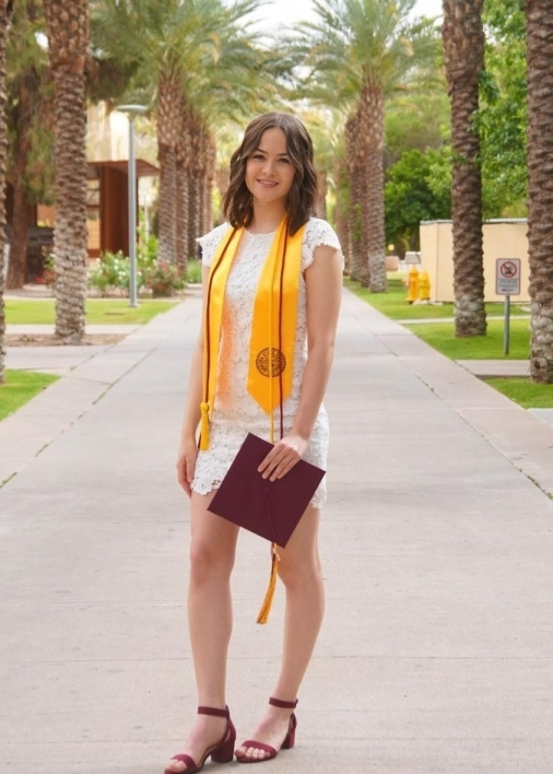 ASU's College of Health Solutions graduate Emma Utagawa smiles while holding her graduation cap on Palm Walk at ASU's Tempe campus