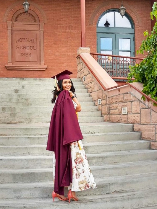 ASU's College of Health Solutions graduate Dulce Vivas Cruz wears her cap and gown as she stands on the staircase at Old Main on ASU's Tempe campus and looks back over her shoulder and smiles