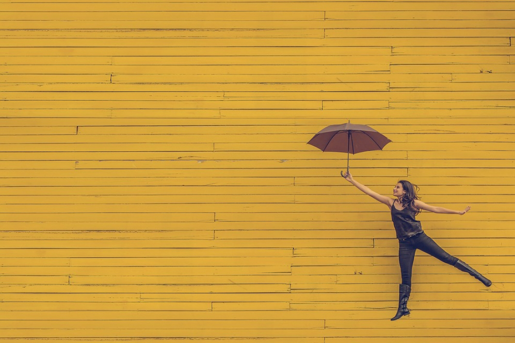 happy woman jumping with umbrella