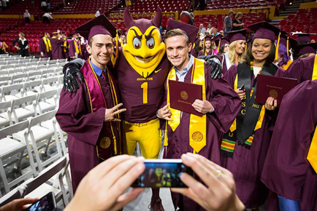 students posing with sparky at convocation