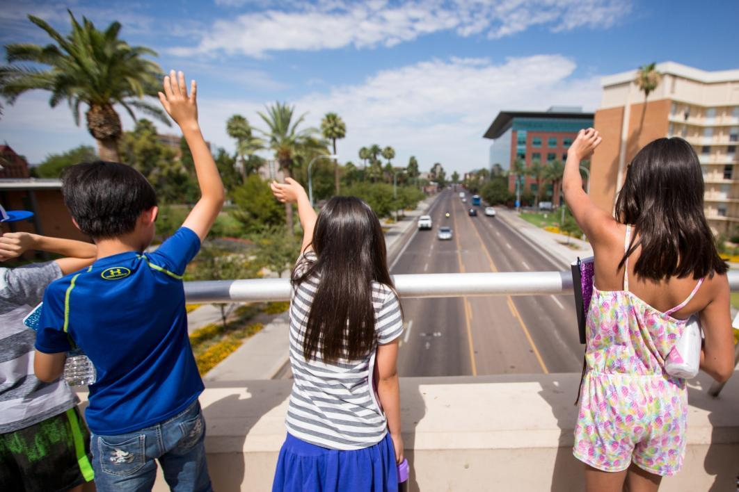 Students wave at traffic while standing on the University Drive bridge during Young Adult Writing Program