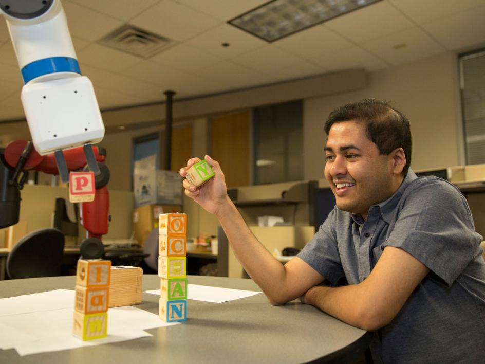 "Tathagata Chakraborti and industrial robot Kramer stack building blocks to fork the words ""Yochan"" and ""plan."""