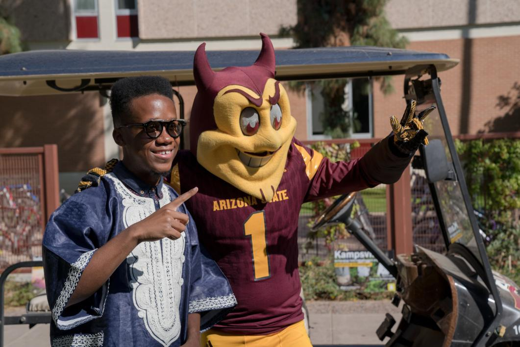 A future ASU student takes a photo with Sparky