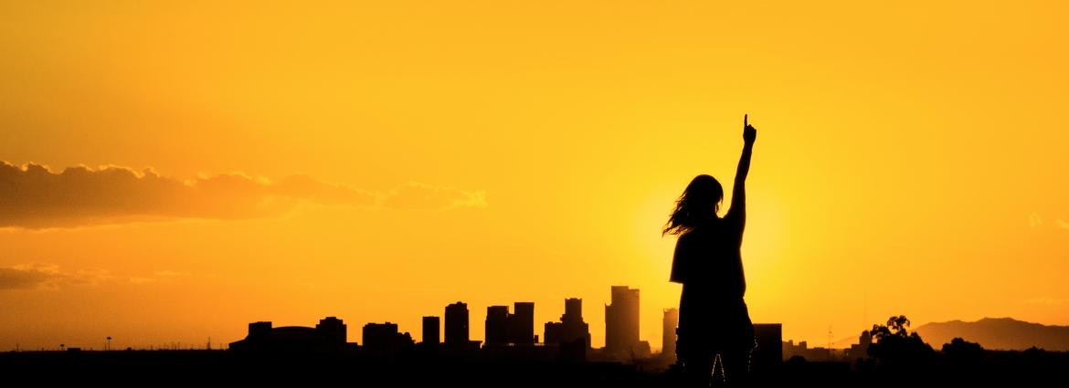Silhouette of a woman pointing at the sky in front of the Phoenix skyline