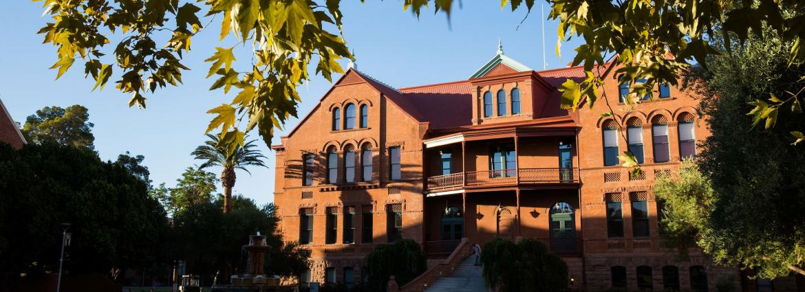 A red brick building is framed by green leaves and shadows.