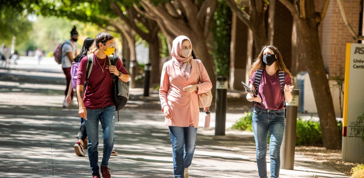 Three students wearing masks talk and laugh as they walk on campus