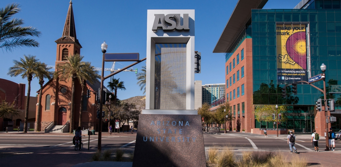An ASU sign shown with the Fulton Center building and a church behind it