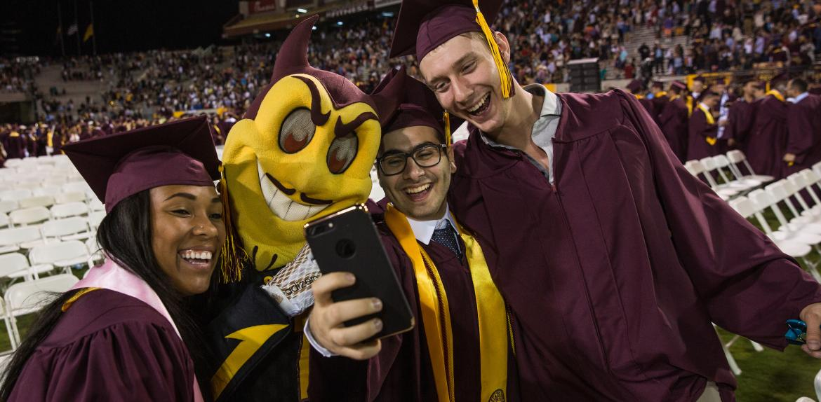 New ASU graduates pose with Sparky at commencement