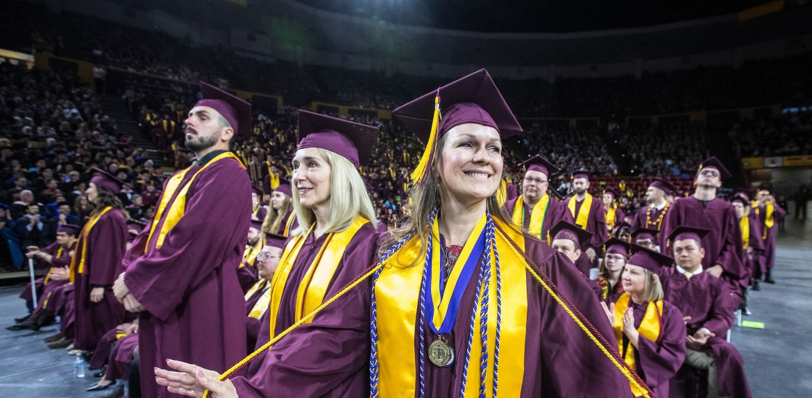 student holding cords out at graduation