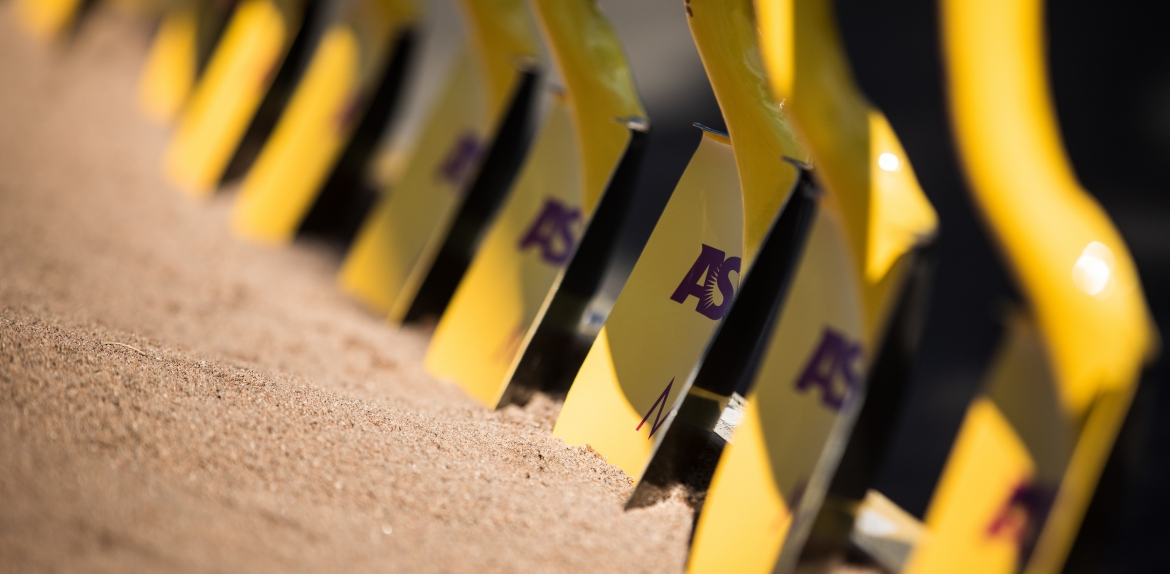 row of shovels in dirt