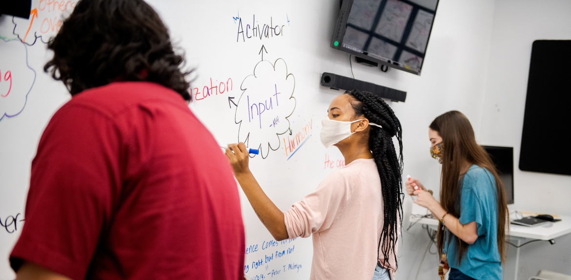 students wearing masks working on whiteboard