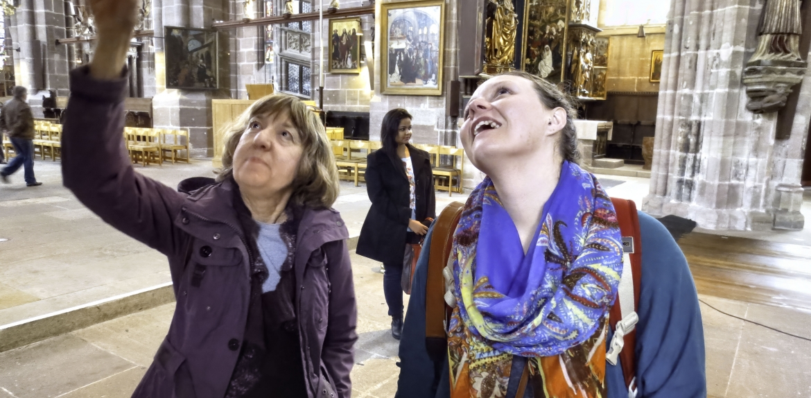 woman pointing up while another woman looks up in an old church