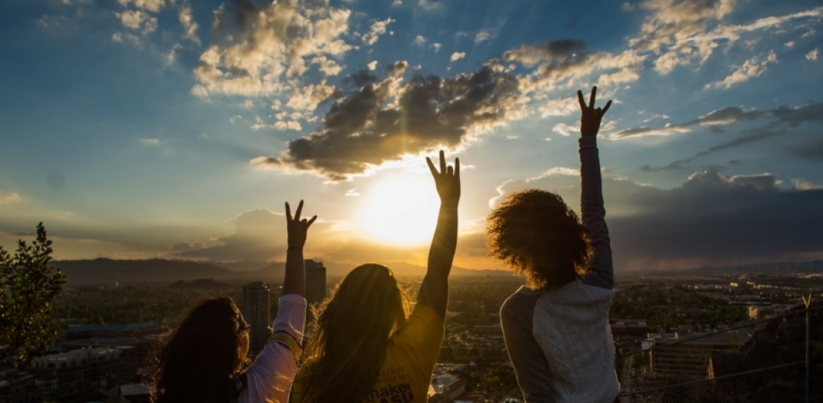 three women pictured from behind as they raise their hands toward a sunset