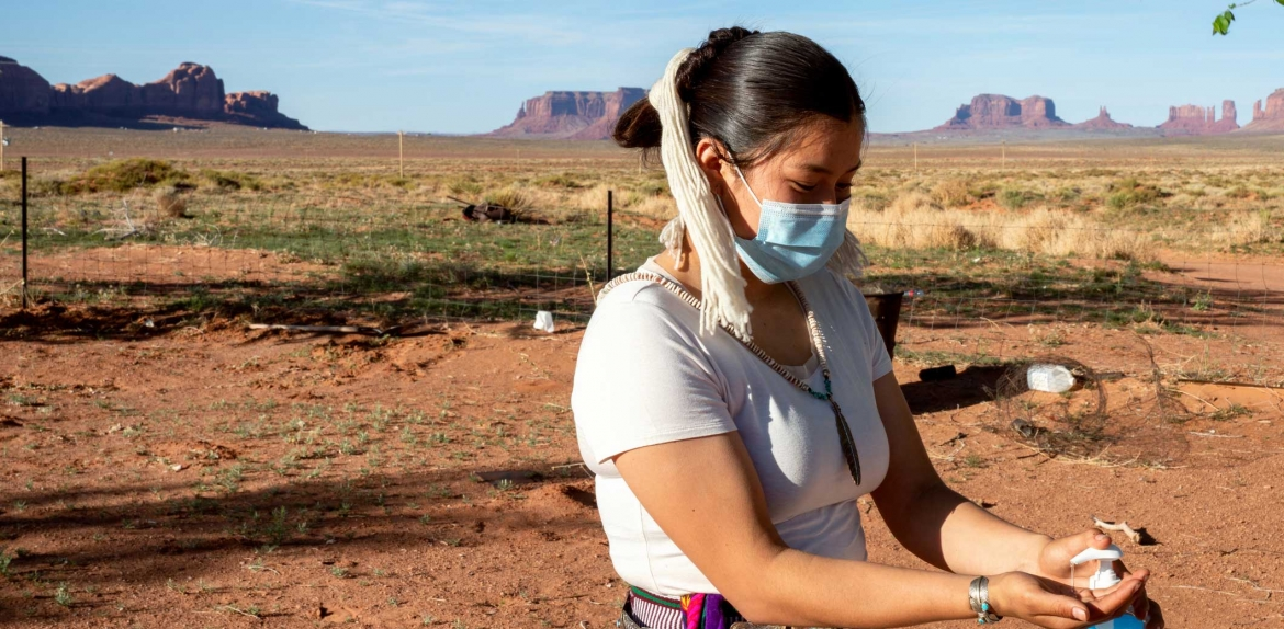 iStock photo of a Navajo woman using hand sanitizer