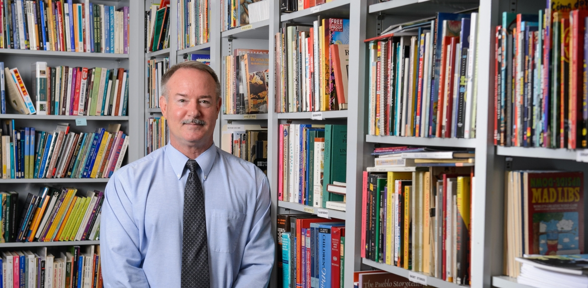 ASU English Professor James Blasingame standing in his office surrounded by shelves of books