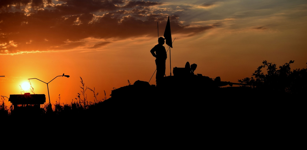 A man on top of military equipment is silhouetted against a sunset sky