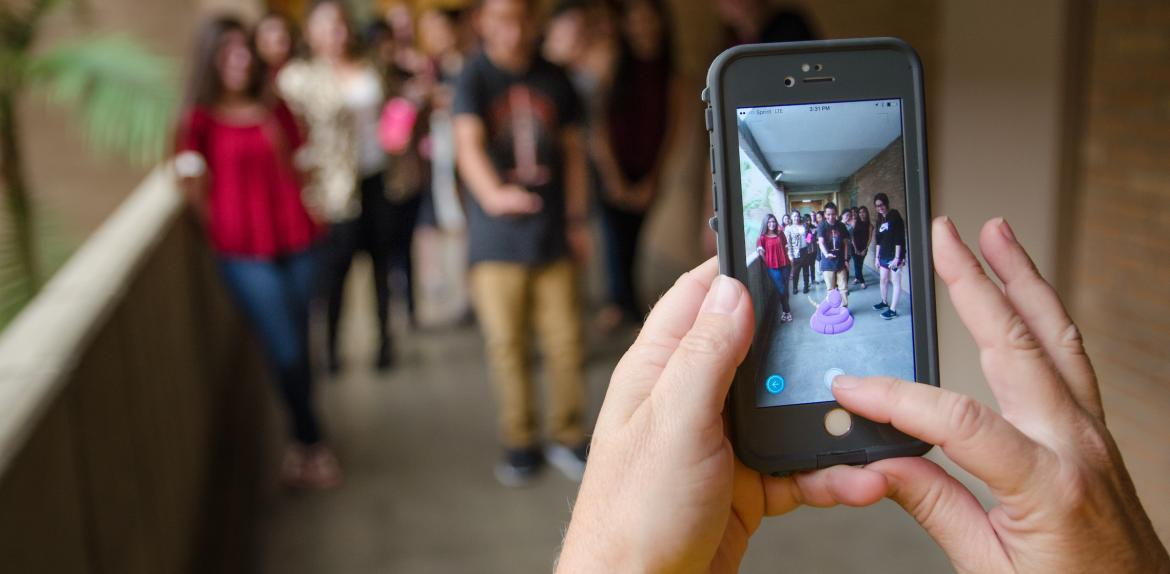 A cellphone takes a photo of a group of students with a Pokemon