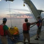 Crew on a ship retrieve a smaller, autonomous underwater vehicle out of the ocean using a winch