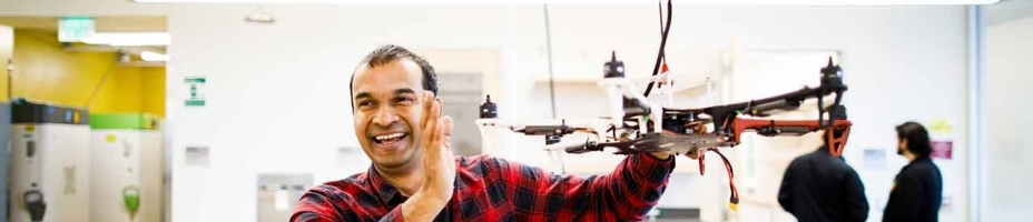 ASU Assistant Research Professor Jnaneshwar Das smiling and holding a drone