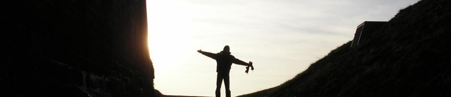 person with outstretched hands looking at sky