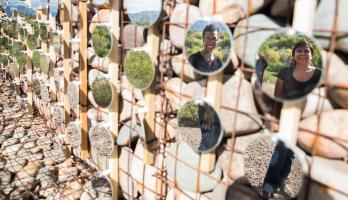 two people reflected in circular mirrors as part of a desert installation