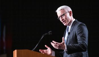 Anderson Cooper speaks at a lectern at an ASU Cronkite award luncheon