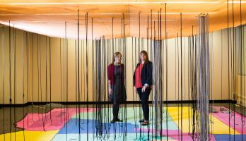 two women standing on exhibit of AZ map on floor with black strings hanging from ceiling